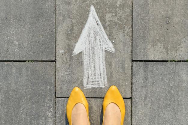 Znak strzałki namalowany na szarym chodniku z nogami kobiet