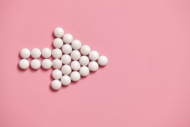 Znak strzałki wyłożony białymi okrągłymi tabletkami