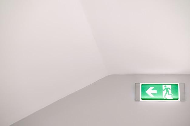 Znak świetlny ewakuacji przeciwpożarowej z biegnącym mężczyzną i strzałką na ścianie pod sufitem