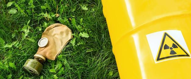 Znak symbolu zagrożenia promieniowaniem, z bliska. znak nuklearny na żółtej metalowej beczce na zielonej trawie, obok niej maska gazowa.