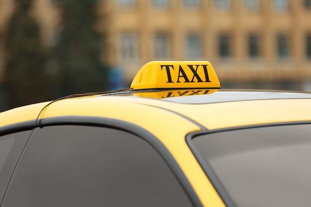 Znak taksówki na żółtym dachu samochodu, zbliżenie