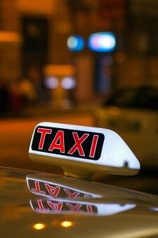 Znak taksówki z taksówki zaparkowanej na ulicy w mediolanie w nocy
