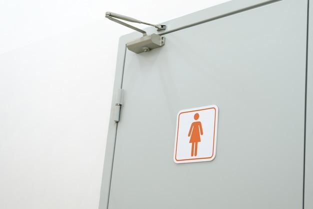 Znak toalety na drzwiach toalety. znaki do toalety dla kobiet. łazienka damska na białej ścianie