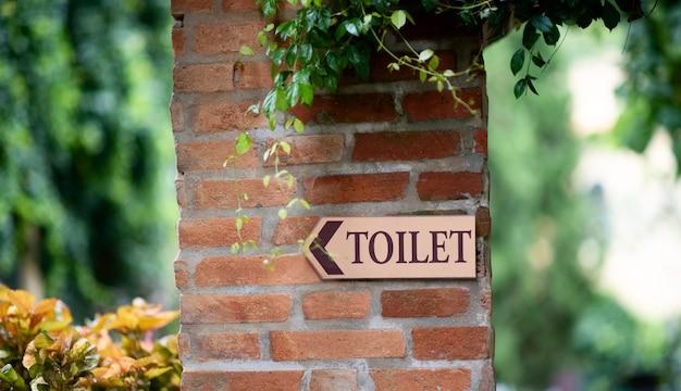 Znak toalety na ścianie czerwonej cegły z liśćmi