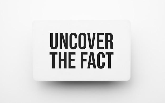Znak uncover the fact na notatniku na białym tle