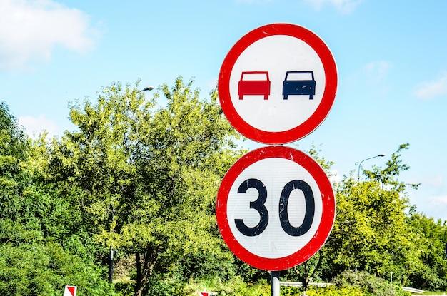 Znak wskazujący ograniczenie prędkości do trzydziestu i zakaz wyprzedzania na zielonych drzewach