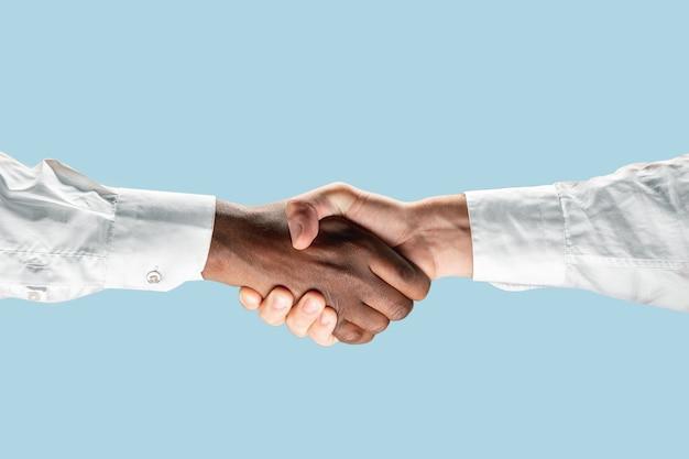 Znak wspólnych planów na przyszłość. praca zespołowa i komunikacja. dwa męskie dłonie drżą na białym tle na niebieskim tle.