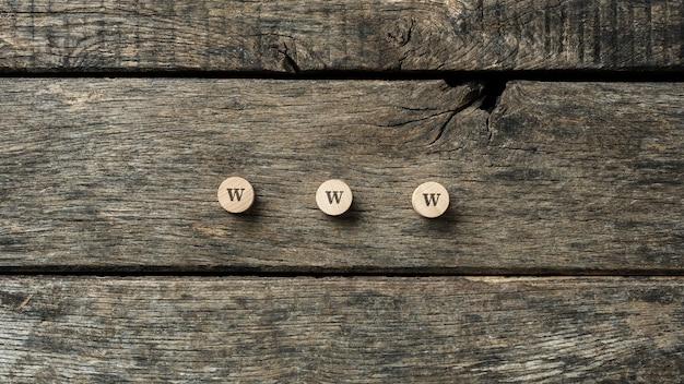 Znak www zapisany na trzech drewnianych wyciętych kółkach umieszczonych na rustykalnych deskach.
