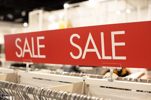 Znak z napisem sprzedaż w kolorze białym na czerwonym tle na parkiecie sklepu z odzieżą casual