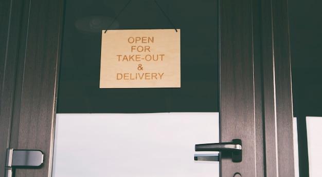 Znak z otworem na wynos i dostawę zawieszony na drzwiach