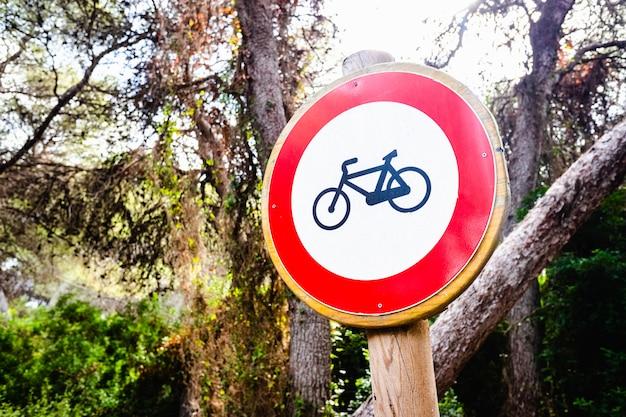 Znak zabroniony do jazdy na rowerze, umieszczony w lesie.
