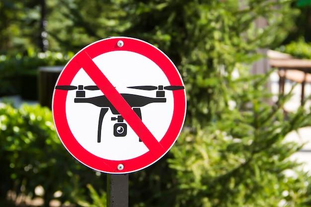 Znak zakazujący lotu dronów na tle zielonej roślinności