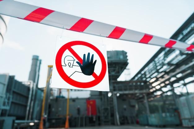 Znak zakazujący przechodzenia osób postronnych na plakacie z biało-czerwoną wstążką.