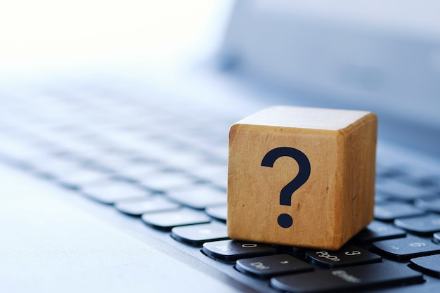 Znak zapytania na drewnianej kostce na klawiaturze komputera, na rozmytym tle i małej głębi ostrości.