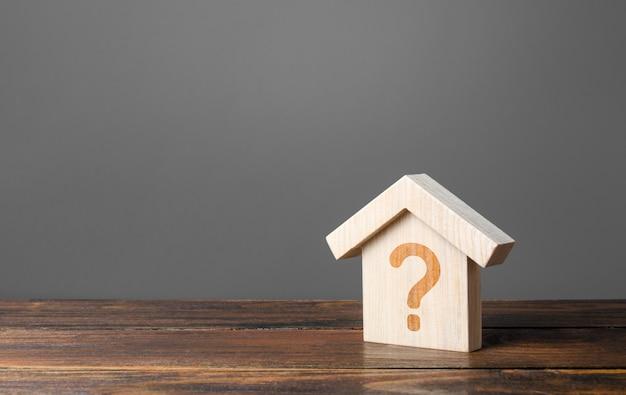 Znak zapytania na drewnianym domu. oszacowanie kosztów. rozwiązywanie problemów mieszkaniowych, decydowanie się na zakup