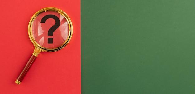 Znak zapytania przez lupę na czerwonym i zielonym banerze q i znajdowanie odpowiedzi koncepcja tło z...