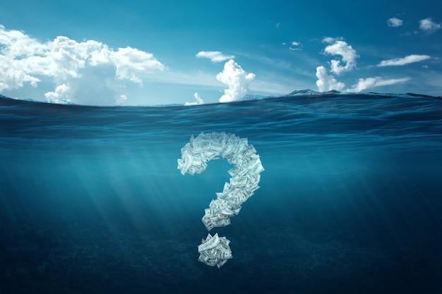 Znak zapytania z dolarów tonie pod wodą. koncepcja kryzysu finansowego, długi, płacenie rachunków, hipoteka, upadłość.