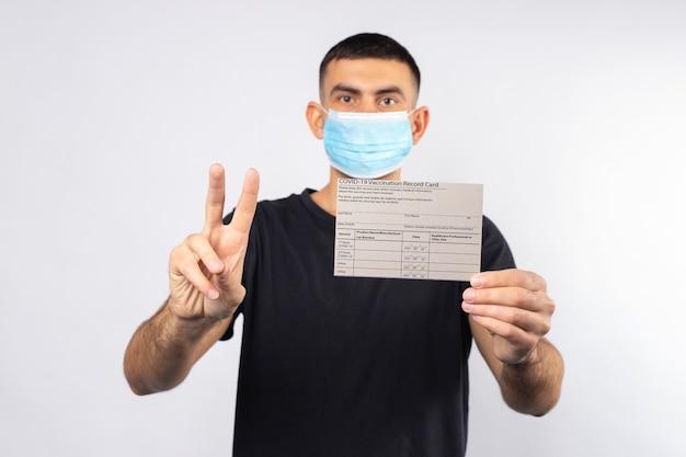 Znak zwycięstwa podczas pandemii mężczyzna w masce medycznej trzyma na białym tle kartę szczepień na koronawirusa