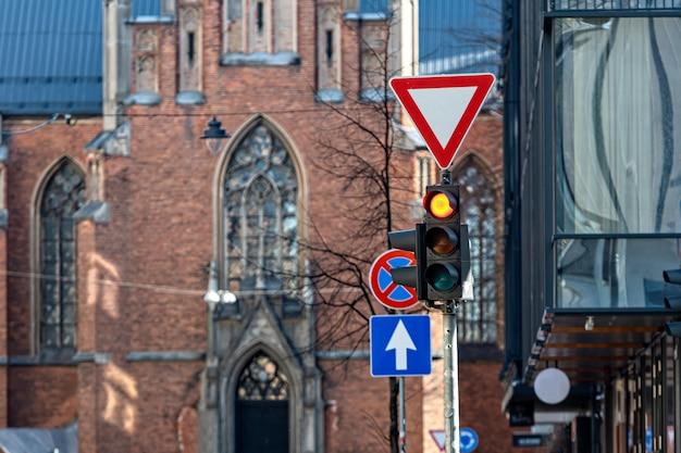 Znaki drogowe i semafor z czerwonym światłem na tle miejskim, zbliżenie