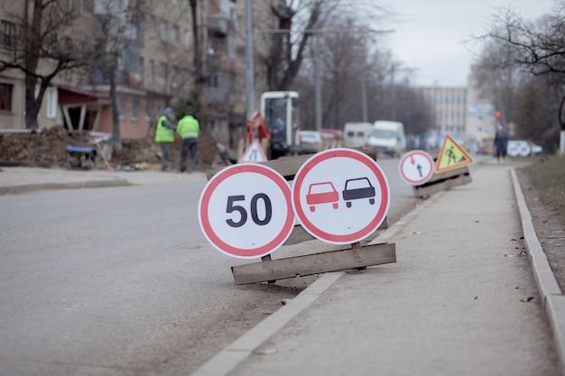 Znaki drogowe, objazd, naprawa dróg na tle ulicy, ciężarówka i koparka kopanie dziury
