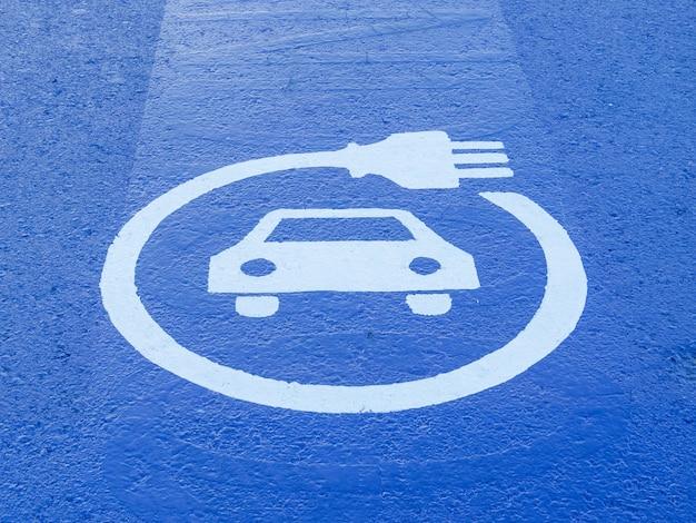 Znaki naziemne wskazujące punkt zasilania samochodu elektrycznego