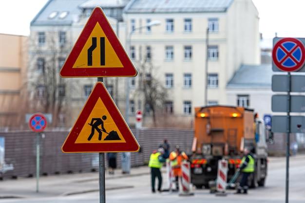 Znaki ostrzegawcze o naprawach ulicznych na rozmytym tle z pracownikami naprawczymi, zbliżenie
