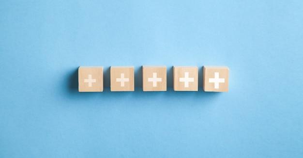 Znaki plus na drewnianych kostkach. pozytywne, korzyści, rozwój