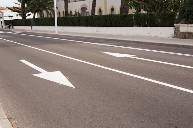 Znaki strzałkowe jako oznaczenia drogowe na ulicy z dwoma pasami ruchu.
