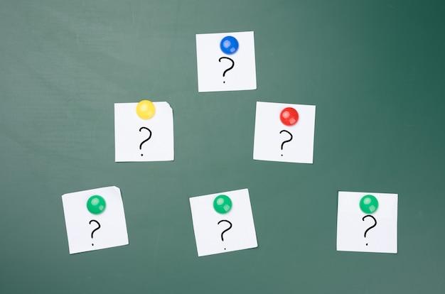 Znaki zapytania są rysowane na białych kawałkach papieru, zielona tablica kredowa