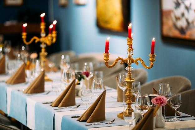 Znakomicie nakryty stół restauracyjny ze świecami i kwiatami