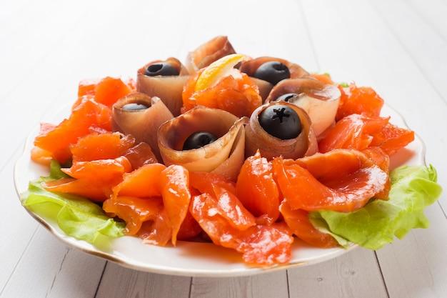 Znakomita restauracja serwująca talerz wędzonej soli, surowych białych filetów rybnych i łososia