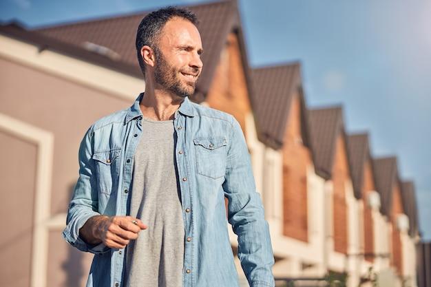 Znakomity mężczyzna pozuje w pobliżu swojego nowego mieszkania