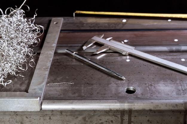 Znakowanie na powierzchni metalowej do wiercenia otworów suwmiarką kwadratową i noniuszową