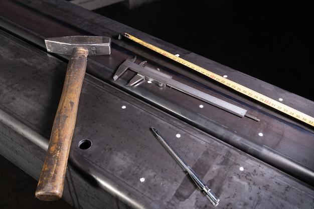 Znakowanie na powierzchni metalowej do wiercenia otworów za pomocą kwadratu i suwmiarki. młot.