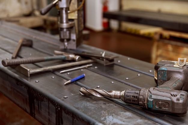 Znakowanie na powierzchni metalowej do wiercenia otworów za pomocą kwadratu i suwmiarki. młotek, przebijak do gwoździ.