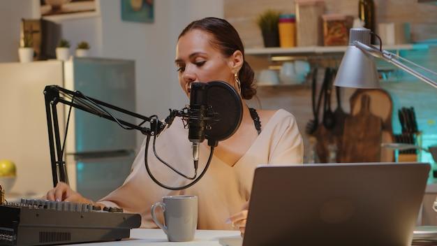 Znana kobieta trzymająca profesjonalny mikrofon podczas nagrywania podcastu dla mediów społecznościowych. internetowa transmisja internetowa na antenie, gospodarz transmisji strumieniowej treści na żywo, nagrywanie cyfrowych komunikatów w mediach społecznościowych