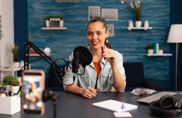 Znany bloger nagrywający recenzję czerwonej szminki na vlog kosmetyczny. kobieta vlogerka udostępniająca samouczek na żywo w mediach społecznościowych za pomocą profesjonalnego mikrofonu, patrzącego na kamerę, aby przygotować cyfrowy podcast
