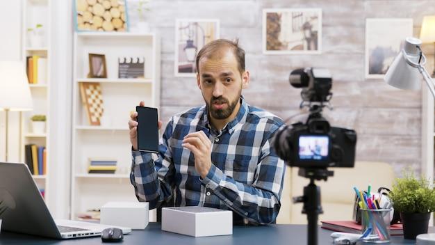 Znany młody influencer nagrywający rozpakowywanie telefonu. twórca treści kreatywnych.