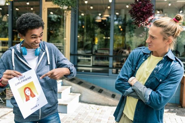 Znasz ją. zadowolony młody człowiek, wskazując na zdjęcie kobiety, stojąc z przyjacielem