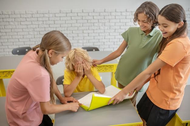 Znęcanie się. chłopiec w żółtej koszulce cierpi z powodu znęcania się nad kolegami z klasy