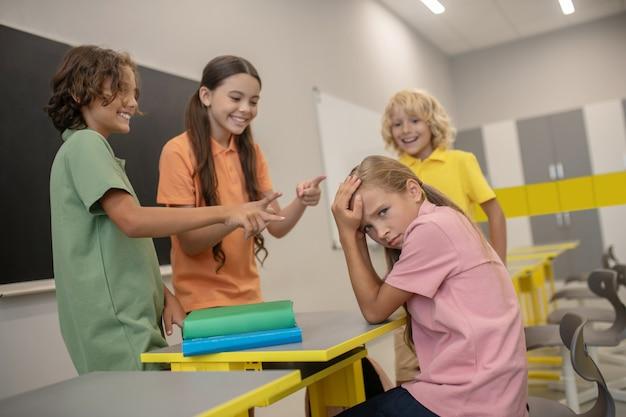 Znęcanie się. dziewczyna w różowej koszulce cierpi na znęcanie się nad kolegami z klasy