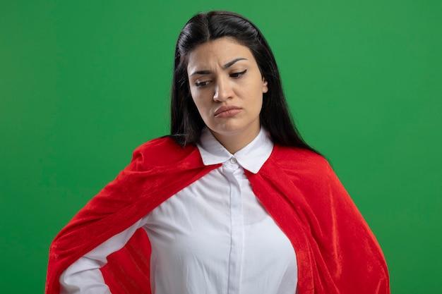 Zniechęcona młoda superwomanka trzymająca rękę na biodrach z przepraszającą twarzą spoglądającą w dół odizolowaną na zielonej ścianie