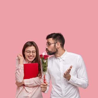 Znienawidzona szczęśliwa kobieta unosi zaciśniętą pięść, pozytywnie chichocze, nosi okrągłe okulary
