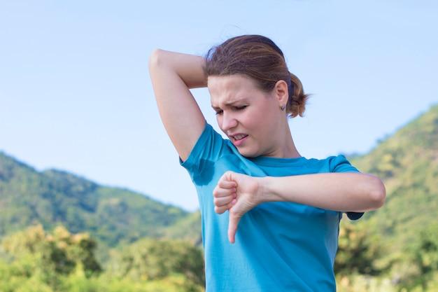 Zniesmaczona dziewczyna, młoda kobieta patrząc na spoconą koszulkę, wąchająca mokre nieczyste pachy, czująca nieprzyjemny zapach potu. koncepcja użycia dezodorantu, niezadowolona dama pokazuje niechęć do kciuka w dół. nadmierna potliwość