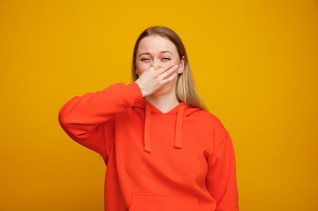Zniesmaczona młoda blondynka robi gest nieprzyjemny zapach