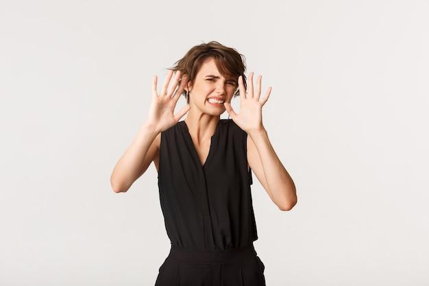 Zniesmaczona młoda kobieta wykrzywiająca się z wzdrygnięcia się, próbująca zasłonić oczy dłońmi, zobaczyć krępującą rzecz stojącą bladą.