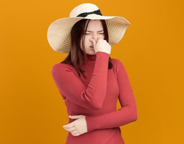 Zniesmaczona młoda ładna dziewczyna w kapeluszu plażowym robi gest nieprzyjemnego zapachu z zamkniętymi oczami, odizolowana na pomarańczowej ścianie z miejscem na kopię