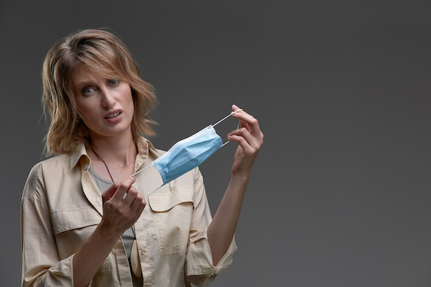 Zniesmaczona zirytowana zła dziewczyna, młoda smutna kobieta patrząca na ochronną maskę medyczną, zdejmij maskę z twarzy. koniec koncepcji pandemii koronawirusa. ncov, covid 19.