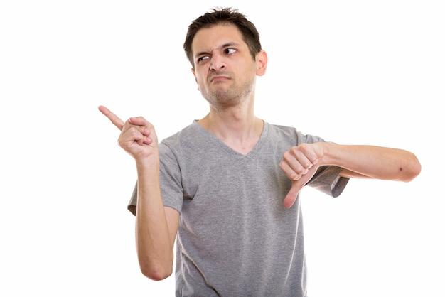 Zniesmaczony młody człowiek wskazujący w lewo i pokazujący kciuk w dół