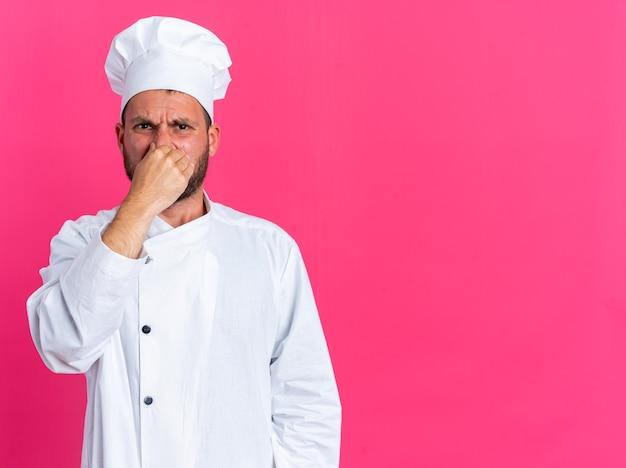 Zniesmaczony młody kaukaski kucharz w mundurze szefa kuchni i czapce patrząc na kamerę robi gest nieprzyjemnego zapachu na różowej ścianie z kopią przestrzeni
